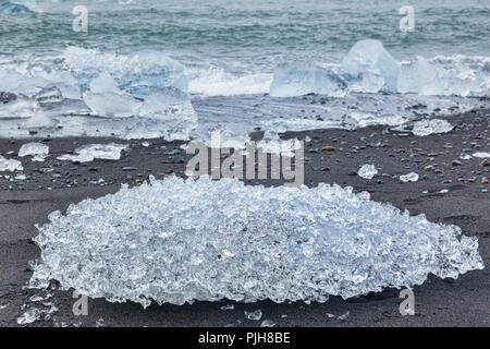 Ice on Diamond Beach, South Iceland, where ice from Jokulsarlon Glacial Lagoon is deposited on the volcanic black sand. - Stock Image