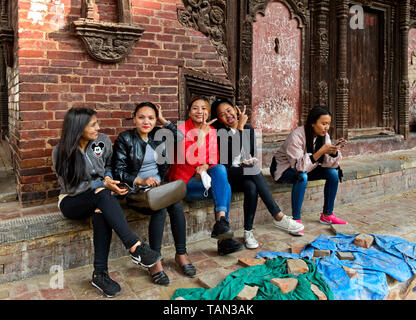 Smiling young Nepelese women sitting on the stairs in front of the Jagannath Temple, Hanumandhoka Durbar square, Kathmandu, Nepal - Stock Image