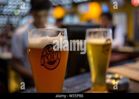 Two glasses of beer at the microbrewery Toit in Bangalore, India. - Stock Image