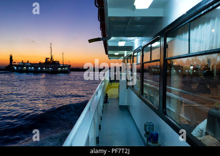 Reflection of the sunset and the ship in the windows of the passenger ferry - Stock Image