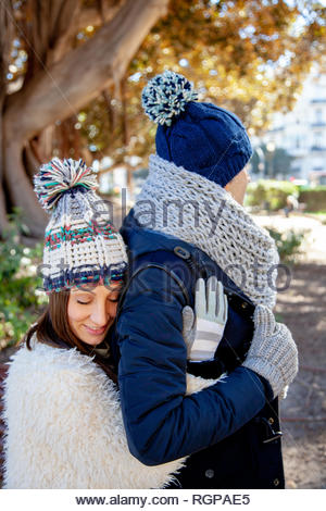 Young woman dressed in winter gloves and woolen hat hugs in love and with eyes closed to her boyfriend from behind - Stock Image