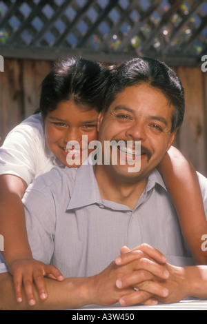 11 year old Mexican American girl hugging father - Stock Image