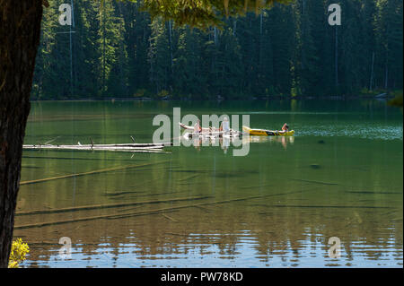 Three unidentified young men and a dog enjoy the waters of Oregon's Hideaway Lake in early fall. - Stock Image