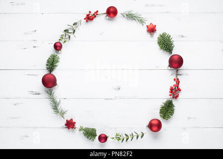 Christmas wreath made of fir branches, balls and eucalyptus on white background. Flat lay - Stock Image
