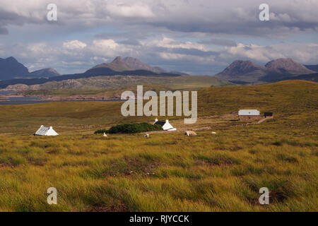 A view of a small ancient crofting community on the Coigach Peninsula, Scotland with sheep in the foreground and mountains in the background - Stock Image