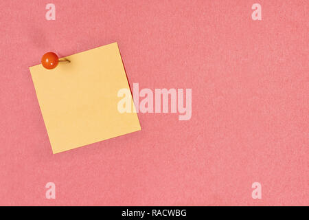 Blank yellow note pad paper over coral color background with free space for text. Image shot from above. - Stock Image