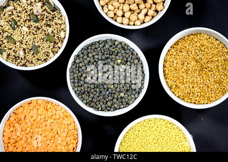 Healthy Selection of Mixed Seeds Sunflower Chia Linseed Couscous Chickpeas Red Green Lentils in White Bowls - Stock Image