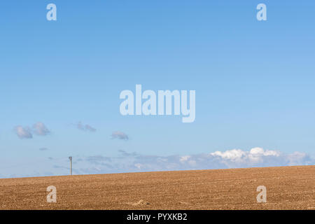 Prepared field (after ploughing) with blue autumnal sky behind. - Stock Image