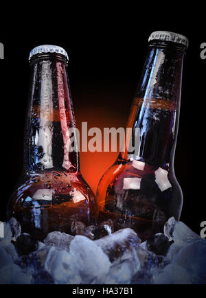 Two cold glass beer bottles are wet with waterdrops on ice with a black isolated background for a bar or party concept. - Stock Image