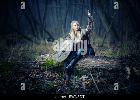 Mad furious viking woman warrior. Sward and shield. Close-up portrait. Book Cover - Stock Image
