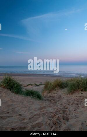 A path winding between the dunes down to a beach in the early morning - Stock Image