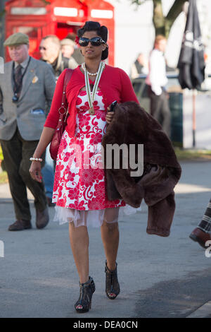 Chichester, West Sussex, UK. 14th Sep, 2013. Goodwood Revival. Goodwood Racing Circuit, West Sussex - Saturday 14th September. A pregnant lady in vintage clothing walks gracefully through the circuit with a fur coat over her arm. Credit:  MeonStock/Alamy Live News - Stock Image