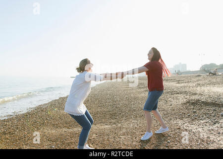 Playful lesbian couple holding hands and spinning on sunny beach - Stock Image