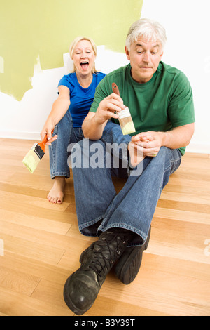 Middle aged couple in front of wall they are painting green while male tries to paint women s toenails with paintbrush - Stock Image