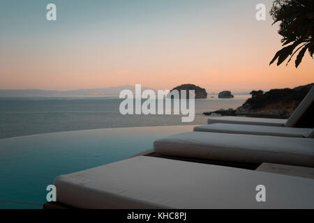 Close up of loungers next to infinity swimming pool on an oceanfront terrace in Mismaloya, Mexico. - Stock Image