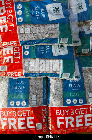 Display of bags of Blue Slate chippings for garden use buy 3 get one free offer in a garden centre - Stock Image