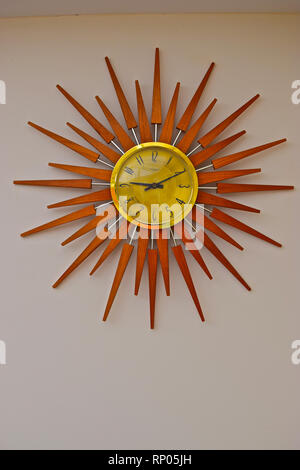 A retro style wall clock with wooden sun shaped surround dating back to the 1970's. - Stock Image