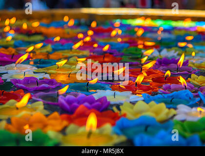burning candles at a Buddhist temple in Thailand - Stock Image