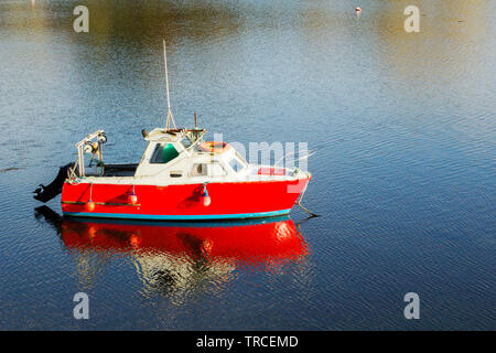 Picture of a small red boat floating on the calm water. - Stock Image
