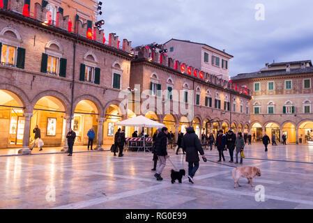 Ascoli Piceno, Italy - December 2018: People walking in winter in Piazza del Popolo, the main city square in Ascoli Piceno, Marche, Italy. - Stock Image