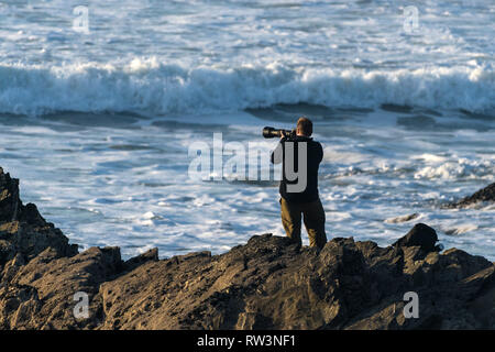 A photographer standing on rocks photographing of the sea. - Stock Image