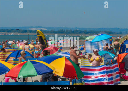 UK's  heatwave and the hottest day of the year as people swarm to crowded West Wittering  beach to cool  off in the Solent ,West Sussex. Hampshire England - Stock Image