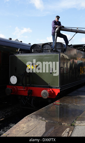 Railway worker filling tender of steam locomotive with water at Sheffield Park station, Bluebell Railway - Stock Image
