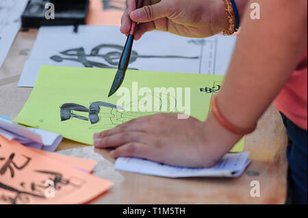 Woman learning to write Chinese characters or letters on colored paper, close up - Stock Image