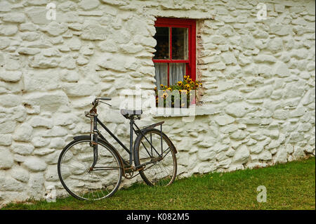 An old bicycle leaning against a lime washed stone building with a red painted window and yellow flowers - Stock Image