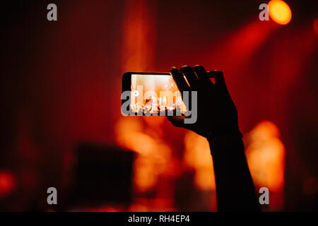 Hand of man in audience video recording concert with camera phone - Stock Image