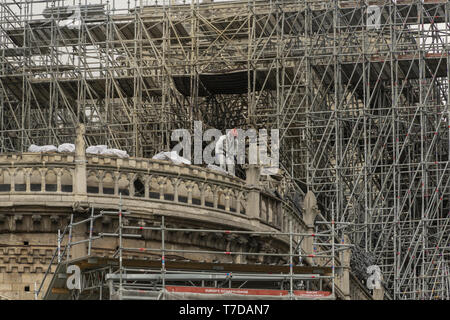 PARIS, FRANCE - 19 APRIL 2019 Notre Dame cathedral, a man removes charred timber from the roof. The remains of the melted scaffolding behind him is wi - Stock Image