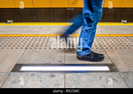 one pedestrian in blue jeans walks on the subway platform along tactile paving also called detectable warning surfaces for visually impaired. yellow - Stock Image