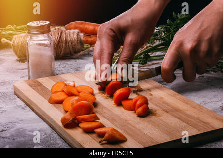 Women's hands close up cut carrots for salad on a cutting board in the kitchen - Stock Image