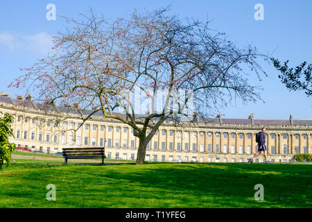 Bath, UK, 29th March, 2019. A man enjoying the warm sunshine is pictured walking in front of the Royal Crescent. Credit:  Lynchpics/Alamy Live News - Stock Image