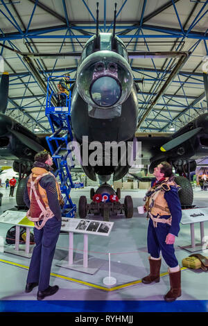 London, UK. 14th March, 2019. Re-enactors in front of the Lancaster - Immersive Histories: Dambusters Virtual Reality Experience. An opportunity to step back in time to the early hours of 17 May 1943 and on board Avro Lancaster G-George to join the Dambusters on their legendary mission. Using the latest virtual reality and haptic technology, in conjunction with a physical 1:1 recreation of the interior of the iconic Avro Lancaster bomber. Credit: Guy Bell/Alamy Live News Credit: Guy Bell/Alamy Live News - Stock Image