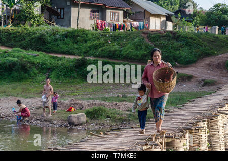 A woman and her child crossing a bridge in Luang Namtha, Laos - Stock Image