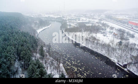 It is snowing in Vilnius, Lithuania, aerial top view of Neris river in winter - Stock Image