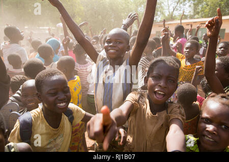 Samba village, Yako Province, Burkina Faso: Children celebrate after their school wins an inter-school football match. - Stock Image