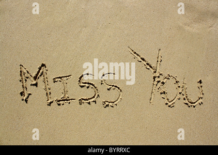 'Miss you' written out in wet sand. Please see my collection for more similar photos. - Stock Image