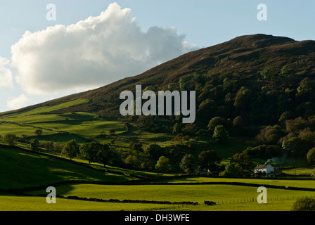 A distant farmhouse with smoking chimney in cumbria set in a a valley surrounded by hills on a bright sunny autumn day. - Stock Image