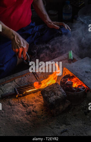 A Silversmith leans over a forge as he makes a silver ring, Shan state, Myanmar. - Stock Image