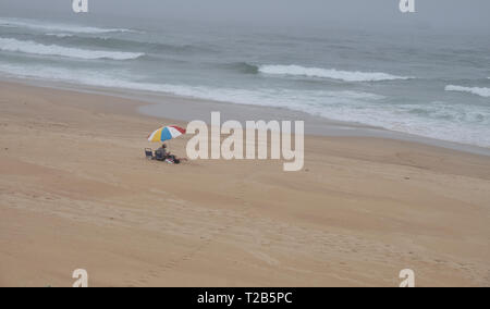 Beach with one single umbrella on a cloudy autumn day.  Desolate capture, with only couple visible under the umbrella - Stock Image