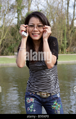 Young Thai  Woman Standing by a Lake in a Park - Stock Image