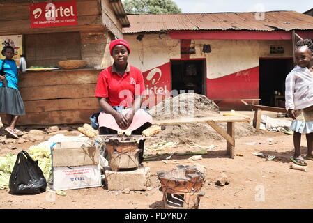 Young Ugandan mother sits on a wooden seat in a small town, selling maize and other crops to earn a living. - Stock Image