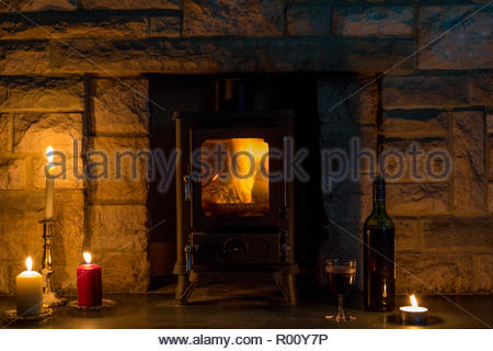 Hygge concept, a log burner, candles, and a wine bottle and glass in a stone fireplace - Stock Image