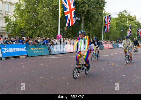 Cyclist in rainbow suit racing along The Mall with onlooking crowd, Brompton World Championships 2018, London, UK - Stock Image