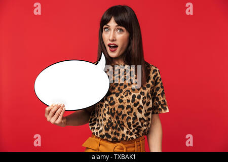 Photo of happy brunette woman 30s dressed in stylish outfit smiling and holding blank thought bubble isolated over red background - Stock Image