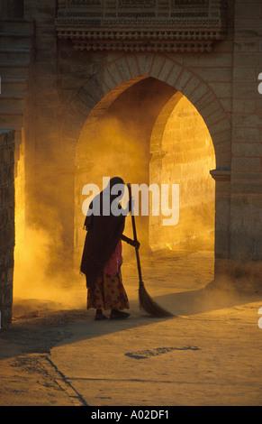 Dawn Sweeper. An Indian woman sweeping dust around a Hindu temple at dawn. Teelon Ki Pol complex near Jaiselmer - Stock Image