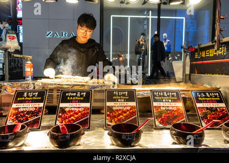 A street food stallholder cooks grilled pork kebabs on his stall in Myeongdong in Seoul, South Korea - Stock Image