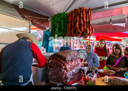Mexican man preparing chorizo and other meats for sale at Mercado el Tepe, a huge urban market in Santiago de Queretaro, Mexico - Stock Image